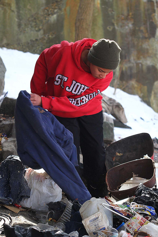 Description of . Jeremy Lundin, 14, the cousin to Jeremiah Oliver's half brothers, searches in the trash under the Rollstone street bride for Jeremiah who has not been sen since Sept. 14, 2013 during a search on Saturday in Fitchburg. SENTINEL & ENTERPRISE/JOHN LOVE