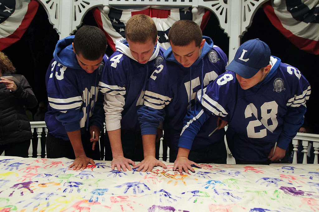 Description of . Leominster High School football players from left sophomore Exavier Torres, senior Nate Nash, junior Max Corbett and junior Evan Valliere put their handprints on the banner that was at the gazebo during the ceremony in support of eighth grader Isaac Phillips sunday night. SENTINEL & ENTERPRISE/ JOHN LOVE