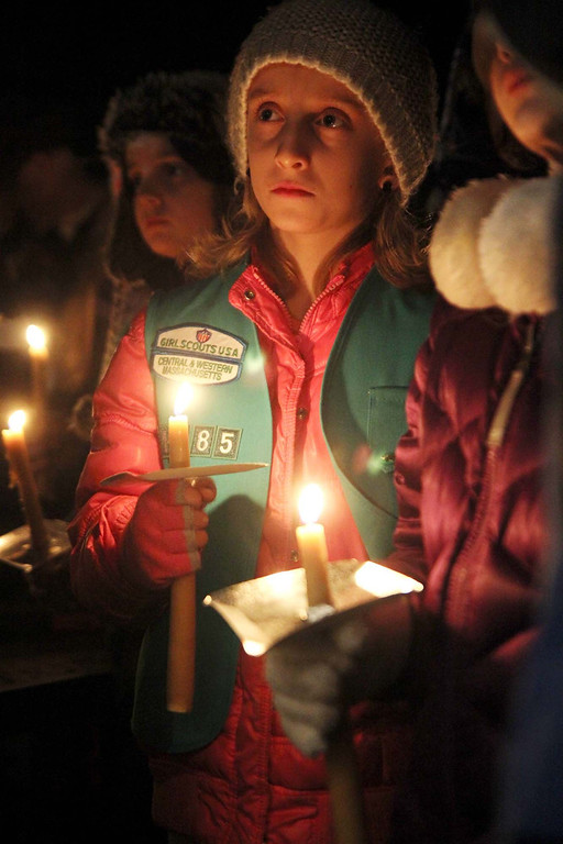 Description of . Lunenburg Girl scout Emily Lavin, 9, with troop 1185 holds a candle at the ceremony in support of Isaac Phillips at the town gazebo on Sunday night. SENTINEL & ENTERPRISE/ JOHN LOVE