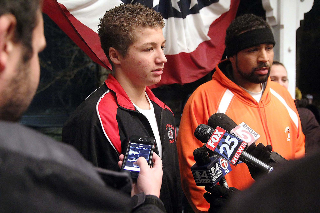 Description of . Lunenburg eighth graders Isaac Phillips talks to the press at the Lunenburg gazebo during a ceremony to support him on Sunday night. Next to him is his father Anthony Phillips. SENTINEL & ENTERPRISE/ JOHN LOVE
