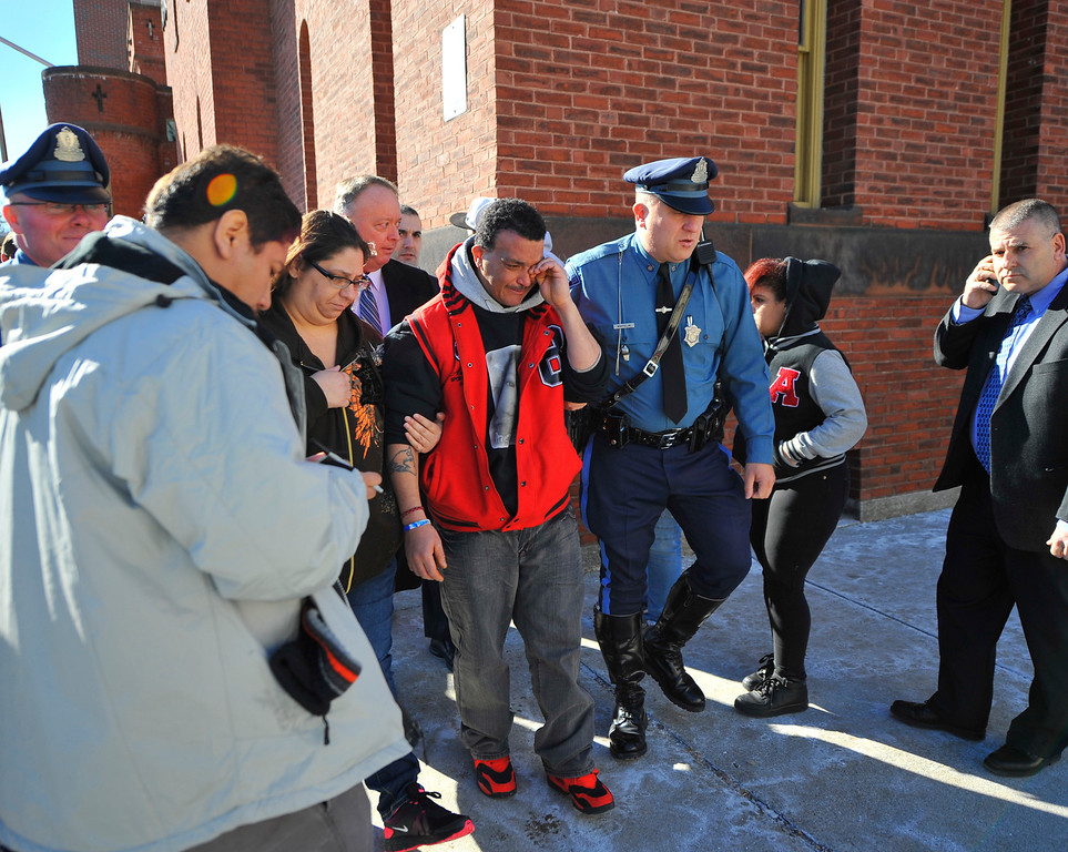 Description of . Sandrino Oliver (center), uncle of missing 5-year-old Jeremiah Oliver of Fitchburg, wipes tears away as he is escorted back into Fitchburg District Court after a verbal outbreak that started in the courtroom following the competency hearing of Elsa Oliver, Friday. Left of Sandrino is Rose Valcourt, Jeremiah's paternal aunt. SENTINEL & ENTERPRISE / BRETT CRAWFORD