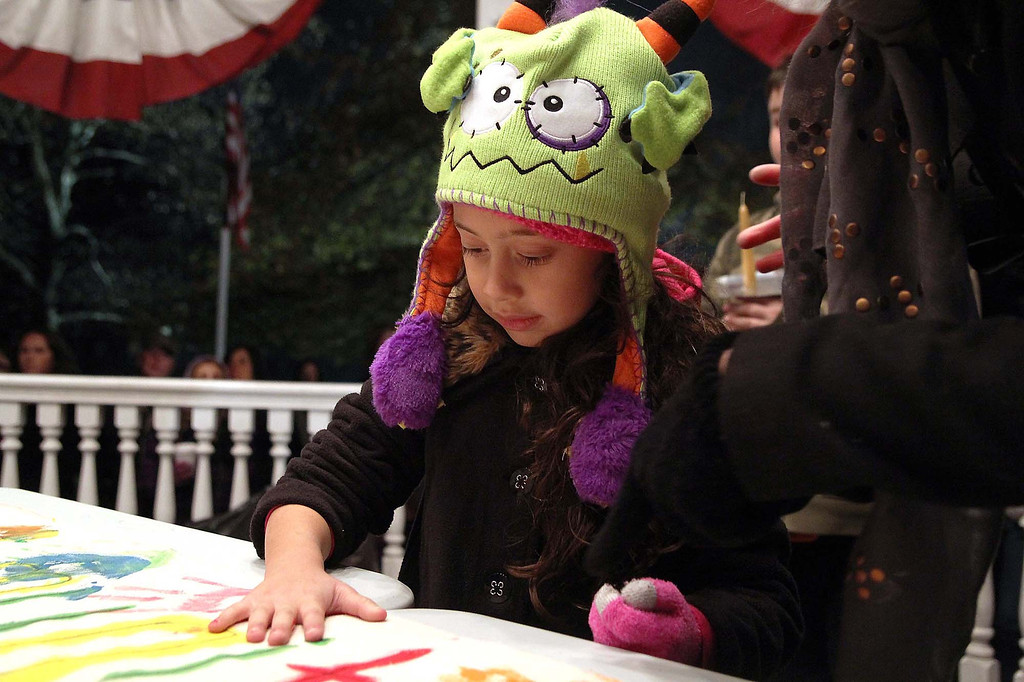 . Victoria Silva Olivera, 6, of Lunenburg puts her handprint on the banner they had out at the gazebo in Lunenburg in support of Isaac Phillips on Sunday night. SENTINEL & ENTERPRISE/ JOHN LOVE