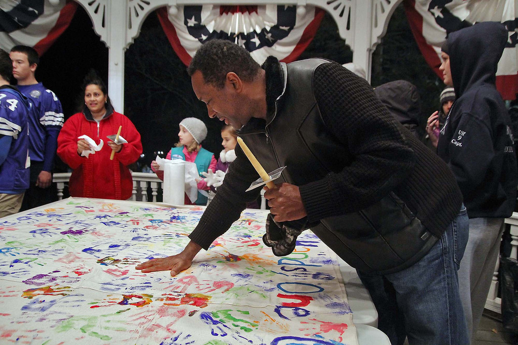 . Mark Williams who has lived in Lunenburg for 24 years and has kids in the school system puts his handprint on the banner they had out at the gazebo in Lunenburg in support of Isaac Phillips on Sunday night. SENTINEL & ENTERPRISE/ JOHN LOVE