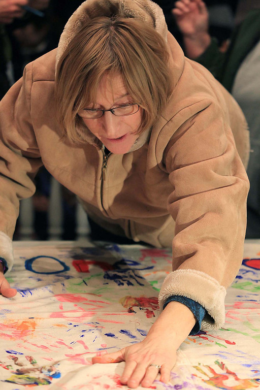 """. Carl Hatch a former Lunenburg School District teacher and how grew up in town puts her handprint on the banner the had out that read \""""many Hands one Community.\"""" SENTINEL & ENTERPRISE/ JOHN LOVE"""