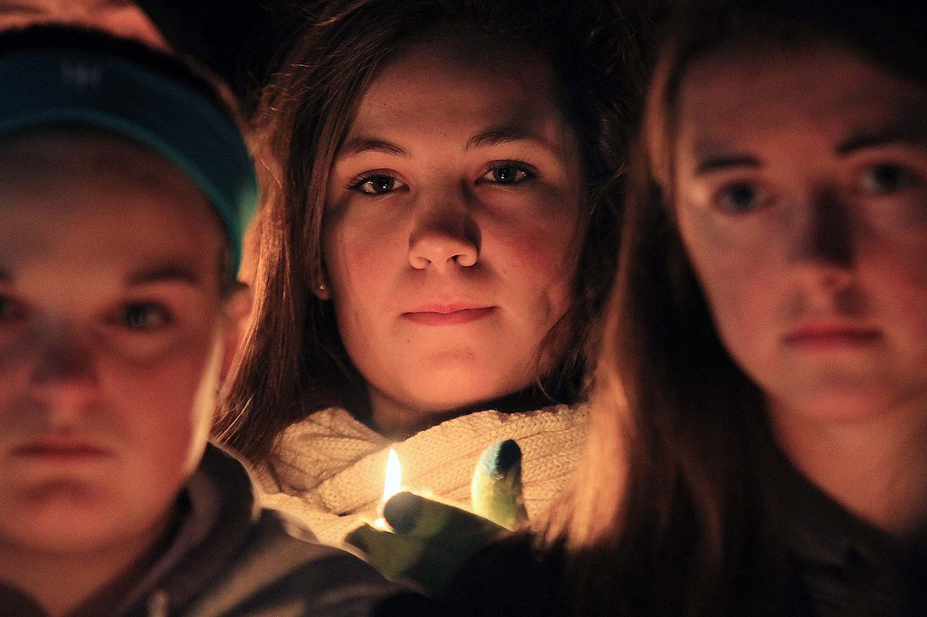 . A young onlooker holds a candle at the ceremony held at the Lunenburg gazebo in support of Lunenburg eight grader Isaac Phillips, 13. SENTINEL & ENTERPRISE/ JOHN LOVE